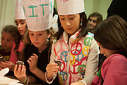 Children decorating chocolate cupcakes at the Kids Zone.