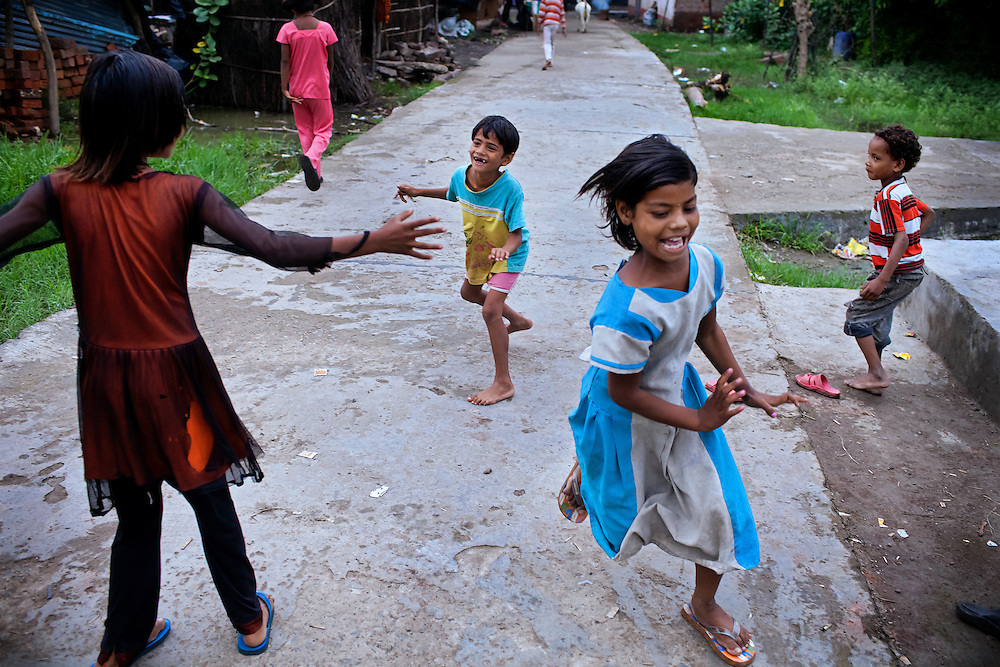 Poonam, 9, (front) is running away from her sister Jyoti, 10, (left) while playing with friends on the streets of Oriya Basti, one of the water-contaminated colonies in Bhopal, central India, near the abandoned Union Carbide (now DOW Chemical) industrial complex, site of the infamous '1984 Gas Disaster'.