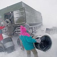 Russian workers load empty fuel drums in storm near Novolazarevskaya science base.