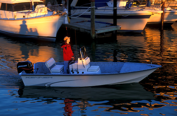 Stock photo of a man pulling his boat in to dock it for the evening