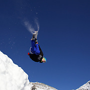A skier takes to the air at The Remarkables Ski Fields, Queenstown, New Zealand during a session with 'The Air Bag'  a large inflatable airbag which breaks the fall of the participant on landing and allows valuable experience and a training aid for Aerial skiers and snowboarders. Queenstown, South Island, New Zealand, 18th July 2011