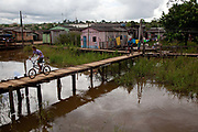 Residents get around the neighbourhood using a series of walkways and platforms over the river water. A third of Altamira in the state of Para, Brazil will be flooded to make way for the Belo Monte dam, nearly all the people affected are the poorest in society or indigenous communities that will have nowhere to go if they were made homeless, and the Government payoff for their properties is low therefore making it difficult to find new accomodation