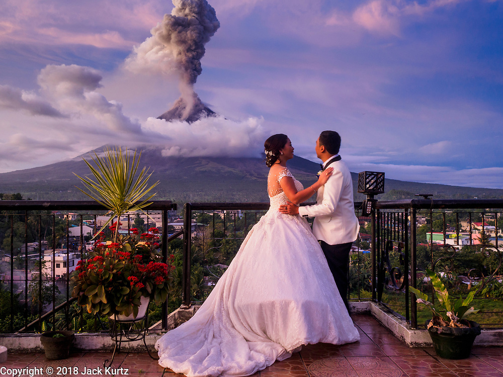25 JANUARY 2018 - DARAGA, ALBAY, PHILIPPINES:  MARIA MAICA DE LA CRUZ and her husband, ARLO GERALD DE LA CRUZ, on their wedding day with the Mayon volcano erupting in the background. They were married earlier in the afternoon at Our Lady of the Gate Parish (Parroquia Nuestra Señora de la Porteria). After their wedding they walked out to Red Labuyo restaurant and the volcano started its eruption. The Mayon volcano continued to erupt Thursday. The airport in Legazpi is closed until at least 31 January 2018. More than 60,000 people have been evacuated because of the volcano.     PHOTO BY JACK KURTZ
