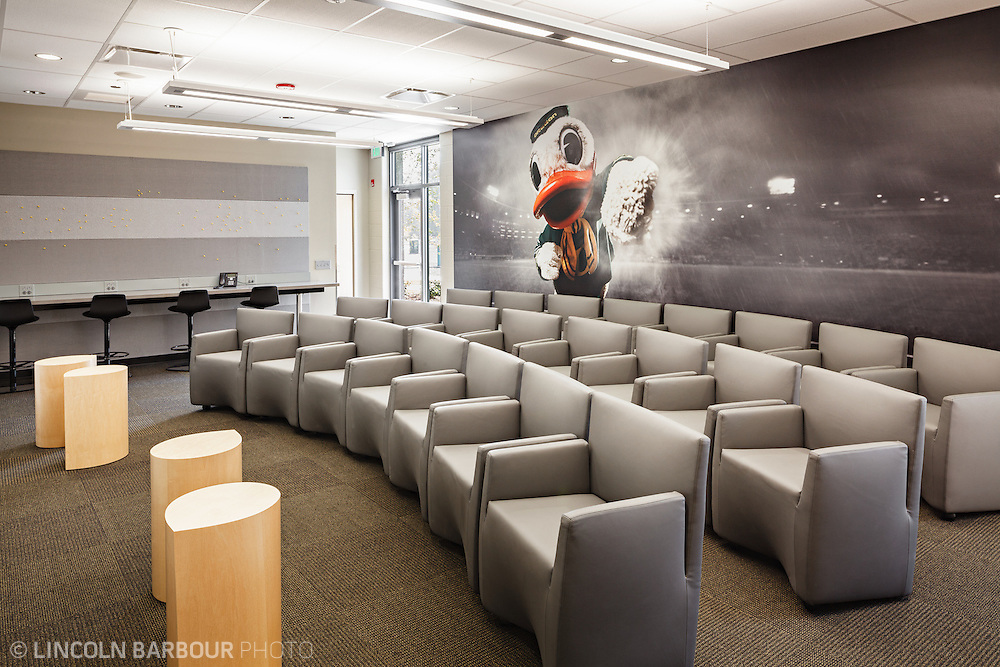 Architectural photo of University of Oregon's Women's Soccer & Lacrosse Stadium. Designed by DLR Group. A media room with a large duck mascot image on the back wall.