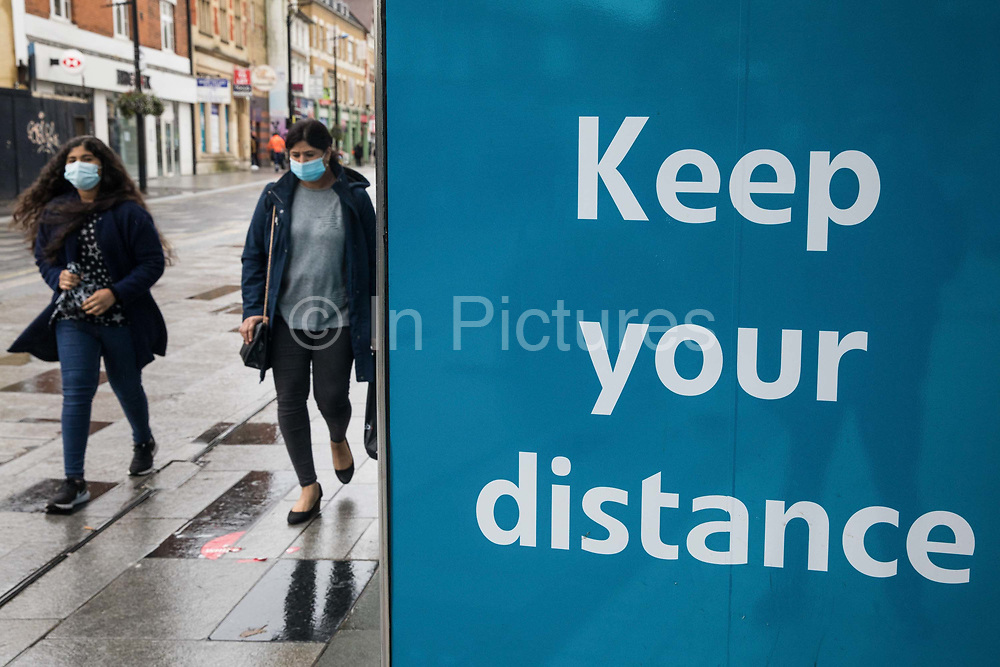 Members of the public wearing face coverings to help prevent the spread of the coronavirus pass a 'Keep your distance' COVID-19 public information display on 4 October 2020 in Slough, United Kingdom. Slough Borough Council confirmed on 2nd October that its coronavirus infection rate is the highest in the south of England and Slough MP Tan Dhesi asked Health Secretary Matt Hancock in Parliament whether the local test centre in Montem Lane could be reverted to permit walk-in and drive-in visits without an appointment.