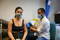 © Licensed to London News Pictures. 25/07/2021. London, UK. Pharmacist, Huseyin Akpinar administers a second dose of the Moderna Covid-19 vaccine to Cristiana Mitrofan at a vaccination centre in Tottenham, north London. Football fans attending Premier League games and other large football matches may need to be fully vaccinated from October, under current government plans. Photo credit: Dinendra Haria/LNP