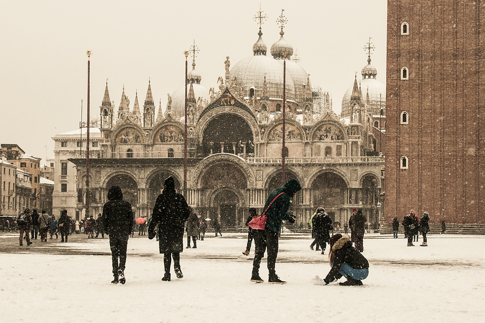 """VENICE, ITALY - 28th FEBRUARY/01st MARCH 2018<br /> Tourists play with the snow during a snowfall in Saint Mark square in Venice, Italy. A blast of freezing weather called the """"Beast from the East"""" has gripped most of Europe in the middle of winter of 2018, and in Venice A snowfall has covered the city with white, making it fascinating and poetic for citizen and tourists.   © Simone Padovani / Awakening"""