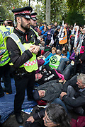 Extinction Rebellion climate change activists who are being cut free from being locked on are surrounded by police as sites around Westminster are blocked on 8th October 2019 in London, England, United Kingdom. Extinction Rebellion is a climate group started in 2018 and has gained a huge following of people committed to peaceful protests. These protests are highlighting that the government is not doing enough to avoid catastrophic climate change and to demand the government take radical action to save the planet.
