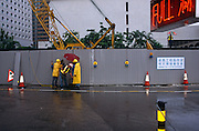 """On the eve of transfer of law in Hong Kong from the UK to China, construction workers in Central Hong Kong carry on their tasks during a monsoonal rain shower on the last day of British rule. Some are dressed in yellow waterproof coats and hard hats, we see a British-style sign warning drivers of Men at Work resembling a man holding an umbrella. Lastly, on the right another man on a wall, also holding an brolley. In the foreground a car park sign states that the space is full in red letters and a local authority sign saying """"Working for a better environment"""" is written in Chinese and English lettering. The transfer of sovereignty of Hong Kong from the United Kingdom to China, referred to as """"The Handover"""" occurred at midnight on June 30, 1997, signifying the end of British rule, and the transfer of legal and financial authority back to China."""