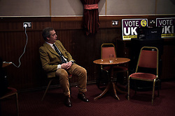 """© London News Pictures. """"Looking for Nigel"""". A body of work by photographer Mary Turner, studying UKIP leader Nigel Farage and his followers throughout the 2015 election campaign. PICTURE SHOWS - Nigel Farage listens to speakers during a public meeting in Margate's Winter Gardens, before going on stage himself, during UKIP's 'Action Weekend' in his constituency of South Thanet, on April 11th 2015. Members of UKIP's youth branch 'Young Independence' came from all over the country to help canvas and distribute UKIP campaign materials during the weekend. . Photo credit: Mary Turner/LNP **PLEASE CALL TO ARRANGE FEE** **More images available on request**"""