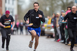 © Licensed to London News Pictures. 13/02/2018. The three hundredth (300) run of the annual Shrove Tuesday Pancake race took place in the centre of Lichfield. The race has run uninterrupted even through both world wars. Pictured, the men's heats. Photo credit: Dave Warren/LNP