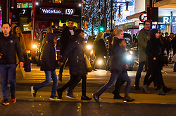 London, December 24 2017. Crowds grow in London's west end on Christmas eve as last minute shoppers hunt for gifts. PICTURED: Shoppers cross the road at Oxford Circus. © SWNS