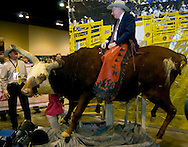 Omaha, Neb 5/6/06 Warren Buffet sits atop a bull at the Justin Boots booth on the floor at the Berkshire Hathaway annual meeting in the Qwest Center Omaha Saturday Morning..(Chris Machian/Prairie Pixel Group)