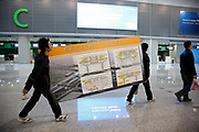 Workers carry an instruction board for airport access through the nearly completed new terminal of the Hongqiao Airport in Shanghai, China on 21 January 2010.  The new terminal is a part of the larger Hongqiao Transportation Hub that will combine air, high-speed rail, and maglev links.