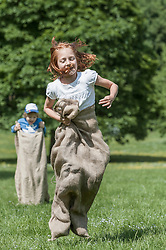 Two girls jumping in sack race in a field, Munich, Bavaria, Germany