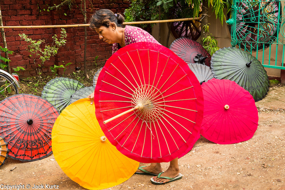 14 JUNE 2013 -  PATHEIN, AYEYARWADY, MYANMAR: A worker sets out waterproof umbrellas  to dry at the Shwe Sar umbrella factory in Pathein. Pathein is a center of the Burmese umbrella and parasol industry. Most are actually parasols made in the traditional Burmese way using treated paper which is not water proof. Shwe Sar's umbrella's are made with treated cloth and are waterproof. Since US and European sanctions have been lifted businesses in Myanmar have seen an explosion in exports. Shwe Sar exports most of their umbrellas to Europe. Pathein, sometimes also called Bassein, is a port city and the capital of the Ayeyarwady Region, Burma. It lies on the Pathein River (Bassein), which is a western branch of the Irrawaddy River. It's the fourth largest city in Myanmar (Burma) about 190 km west of Yangon.   PHOTO BY JACK KURTZ