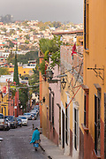 An elderly woman walks past the Spanish colonial style homes along the cobblestone Correo street in the historic center of San Miguel de Allende, Mexico.