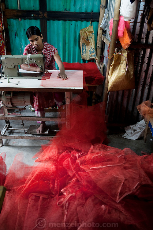A micro-loan recipient stitches net bags destined for Dhaka  at her home in  the village of Bari Majlish, an hour outside Dhaka, Bangladesh. (From the book What I Eat: Around the World in 80 Diets.)  Each bag sells for 1.2 taka ($0.02 USD). In order for a seamstress to make the equivalent of $1 (USD), she must sew 1,000 bags. She received a micro-loan from the Bangladesh Rehabilitation Assistance Committee (BRAC), which provides micro-loans to village women making mesh bags.