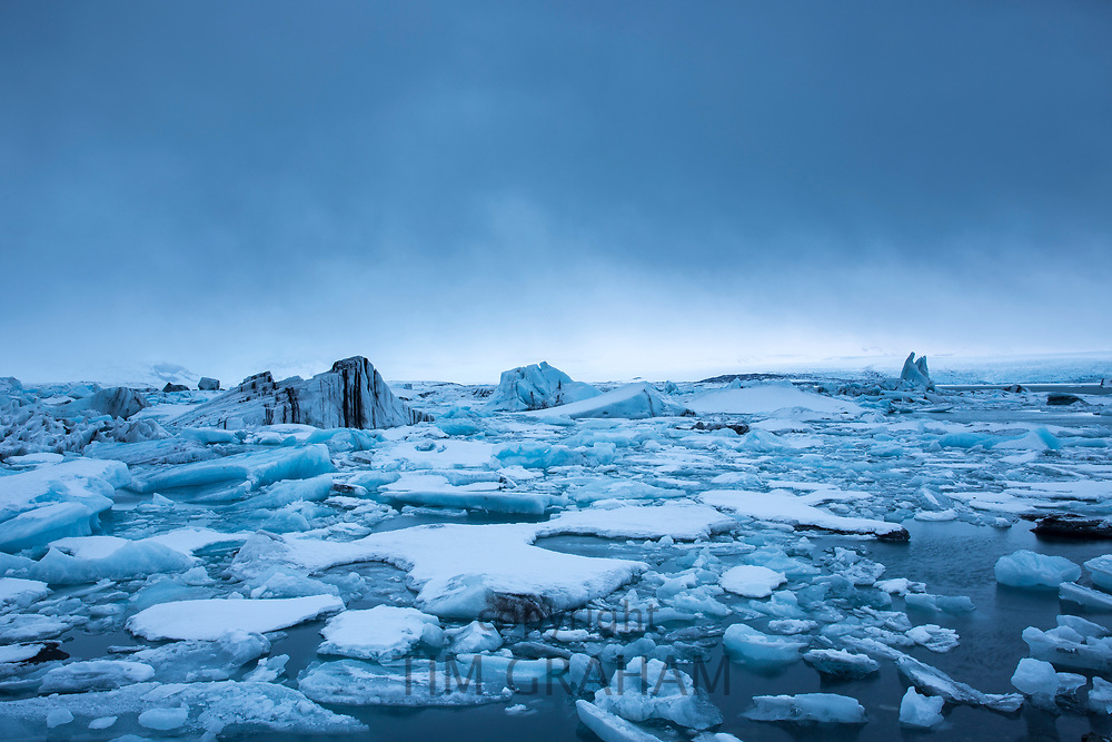 Jokulsarlon glacial lagoon by Vatnajokull National Park. Icebergs floating in blue melt water to the Atlantic Ocean from Breioamerkurjokull Glacier, part of Vatnajokull Glacier in South East Iceland.