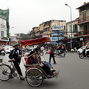 Tourists ride a Bicycle Rickshaw or 'Cyclo' in the old quarter of Hanoi, Vietnam. Hanoi is the capital of Vietnam and the country's second largest city. Hanoi, Vietnam. 17th March 2012. Photo Tim Clayton