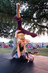 People practicing yoga and acrobatic moves at July 4th celebration on the Trinity Trails near the Panther Island Pavilion, Trinity River, Fort Worth, Texas, USA.