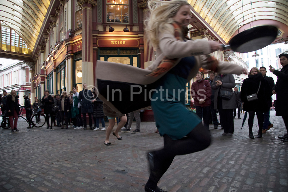 Shrove Tuesday festivities as competitors line up for the Leadenhall Market Pancake Day Race on 13th February 2018 in London, United Kingdom. Competing teams of City workers outside The Lamb Tavern tackle the 25m course, competing to win the coveted frying pan trophy as they flip their wayaround the historic 14th century market.