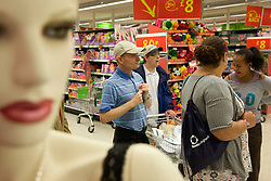 Group of Day Service users with learning disabilities accompanied by a Care Assistant shopping at the supermarket,