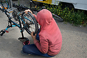 Calais August 2015 The Jungle, camp of migrants, most of whom are trying to get to England. A young boy repairs his bicycle. A charity has donated bicycles and teaches people how to repair them.