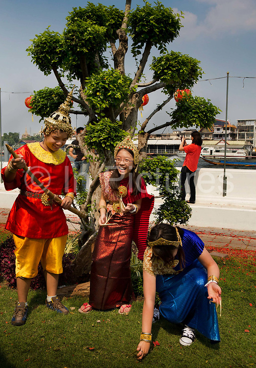 Tourists being dressed in traditional Thai outfits and posing for photographs in the grounds of Wat Arun, a Buddhist temple (wat) in the Yai district of Bangkok, on the west bank of the Chao Phraya River. Wat Arun is among the best known of Thailand's landmarks. The temple is so named because the first light of the morning reflects off the surface of the temple with pearly iridescence. Although the temple had existed since at least the seventeenth century, its distinctive prang (spires) were built in the early nineteenth century during the reign of King Rama II. Thailand.