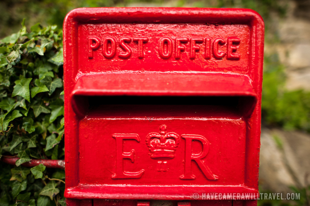 Bright red royal post box in Painswick, England. View from directly in front.