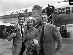 File photo dated 03/06/57 of Hollywood film star Kirk Douglas and his wife Anne Buydens being met by Tony Curtis, left, on their arrival at London Airport from Paris. Douglas is celebrating his 100th birthday today.