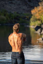 back of a muscular man in a river