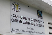 Sign outside the San Joaquin community center reveals the public bathroom project was funded by the BSCFA via its Fairtrade premium funds in 2011. Belize Sugar Cane Farmers Association (BSCFA). San Joaquin, Corozal, Belize. January 23, 2013.