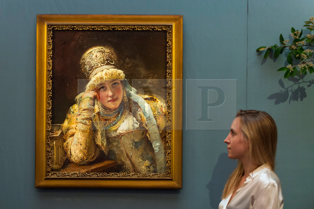 """© Licensed to London News Pictures. 31/05/2019. LONDON, UK. A staff member views """"Boyarina"""" by Konstantin Egorovich Makovsky (Est. GBP 80,000-120,000) at a preview of works from the upcoming sale of Russian Pictures, Works of Art, Fabergé & Icons Sales at Sotheby's, New Bond Street, on 4 June 2019.  Photo credit: Stephen Chung/LNP"""