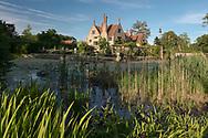 Iris sibirica growing near a moat surrounding the Tudor manor house,  Hindringham Hall, Hindringham, Norfolk, UK