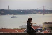 Woman seated on the walls of Saint George Castle in Lisbon, with Tagus River, 25th of April Bridge and the Cristo-Rei (King Christ) landmark.