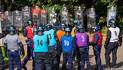 South Queensferry,, Scotland, UK. 16th September 2021. Police Scotland invite the press to witness their ongoing public order training at Craigiehall Camp at South Queensferry. The training is designed to prepare police for the upcoming COP26 event in Glasgow in November where protests are anticipated. Police in riot gear faced up  against police taking the role of protesters throwing missiles and attacking them with clubs.  Pic; Protesters and riot police square off.  Iain Masterton/Alamy Live News.