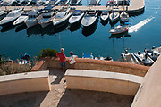 Tourists look at a boat sailing in the harbor of the village of Sperlonga, Italy. Sperlonga is a coastal town in the province of Latina, Italy, about halfway between Rome and Naples.