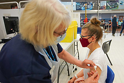 © Licensed to London News Pictures. 31/03/2021. Derby, UK. A member of the public receives the first dose of the Pfizer/BioNTech vaccine at Derby Arena vaccination centre. Photo credit:  Ioannis Alexopoulos/LNP