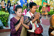 """Offering flowers and incense at the That Luang festival, Vientiane, Lao PDR. Vientiane's most important Theravada Buddhist festival, """"Boun That Luang"""", is held for three days during the full moon of the twelfth lunar month (November). Monks and laypeople from all over Laos congregate to celebrate the occasion with three days of religious ceremony followed by a week of festivities, day and night. The religious part concludes as laypeople, carrying incense and candles as offerings, circumambulate Pha That Luang three times in honor of Buddha."""