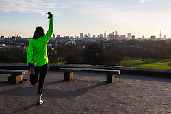 December 11th 2014. A woman does stretching exercises on top of Primrose Hill as early morning sunsine greets Londoners.