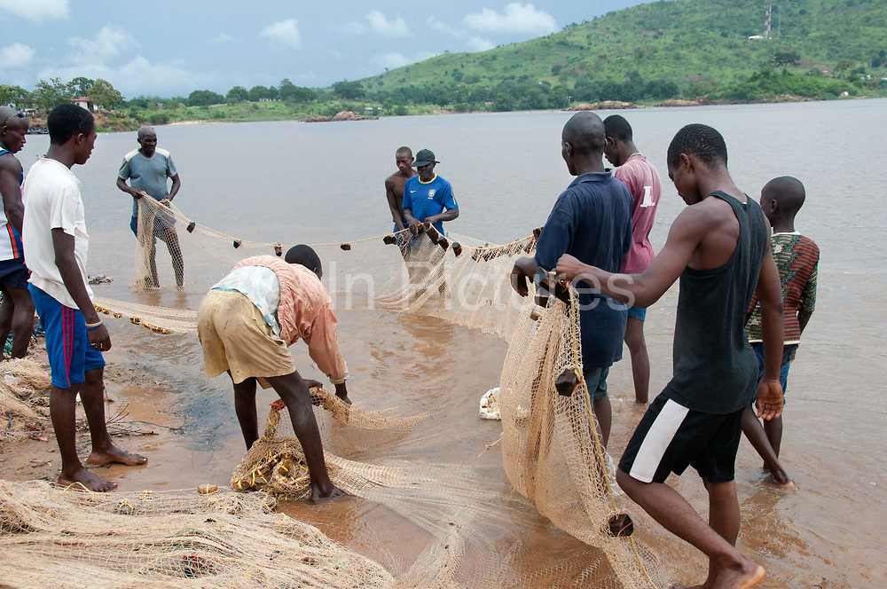 Central African Republic. August 2012. Bangui. Men fishing  in the Ubangui river haul in their net but have not caught anything