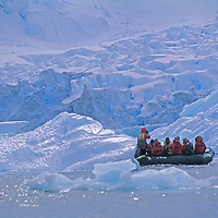 Tourists cruise in a zodiac raft below a glacial icefall on the Antarctic Peninsula, Antarctica.