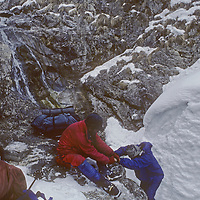 Ski Mountaineers Jay Jensen and Allan Pietrasanta help each other to cross a stream near the end of an the first-ever winter traverse of from Ladakh to Kashmir. Two days earlier the team was caught in a massive avalanche and the photographer - who was able to ski and hike out - did not yet know he was suffering from two crushed vertebrae and a less-serious knee injury.