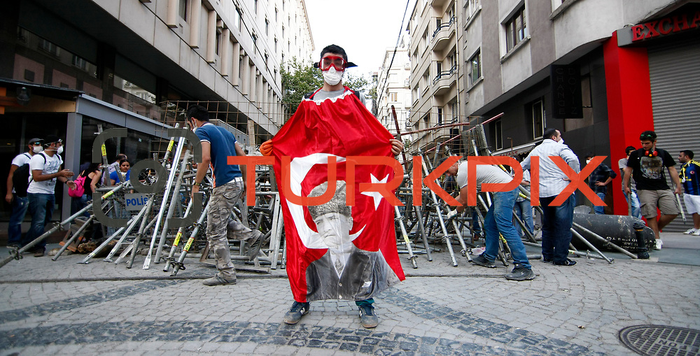 A Protester front a barricade during a protest at Taksim Square in Istanbul June 11, 2013. Turkish riot police fired tear gas and water cannon at hundreds of protesters armed with rocks and fireworks on Tuesday as they tried to take back control of a central Istanbul square at the heart of fierce anti-government demonstrations. Photo by AYKUT AKICI/TURKPIX