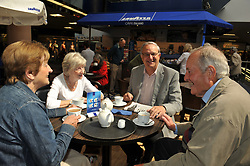 Pensioners enjoy tea in a busy Cafe in a shopping centre