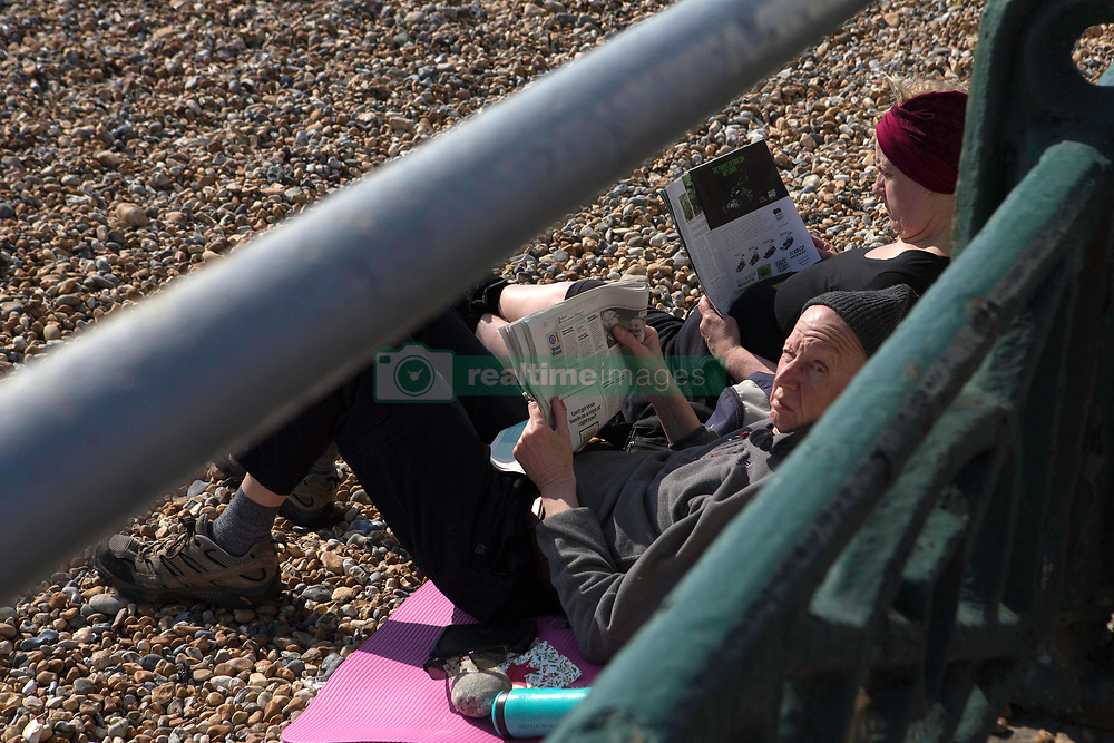 People read while sunbathing on the beach in Brighton, East Sussex, as the UK continues in lockdown to help curb the spread of Coronavirus.
