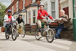 Young people riding bikes on the pavement.