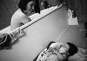 """""""Eye Contact."""" A mother peers over the bath to keep watch over her five month-old baby daughter who is lying on a matt, holding a towel to her face. The infant has had her own time in the water and the mum has taken the opportunity to bathe too. They both look into each other's eyes in a picture of love, trust and joy. This is from a documentary series of pictures about the first year of the photographer's first child Ella. Accompanied by personal reflections and references from various nursery rhymes, this work describes his wife Lynda's journey from expectant to actual motherhood and for Ella - from new-born to one year-old."""