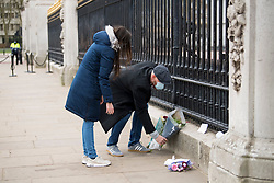 © Licensed to London News Pictures. 10/04/2021. London, UK. Mourners place flowers at the gates of Buckingham Palace at first light, the morning after the death of Prince Philip, The Duke of Edinburgh. Yesterday (Fri) The British Royal Family announced the death of The Duke of Edinburgh, at the age of 99. Photo credit: Ben Cawthra/LNP
